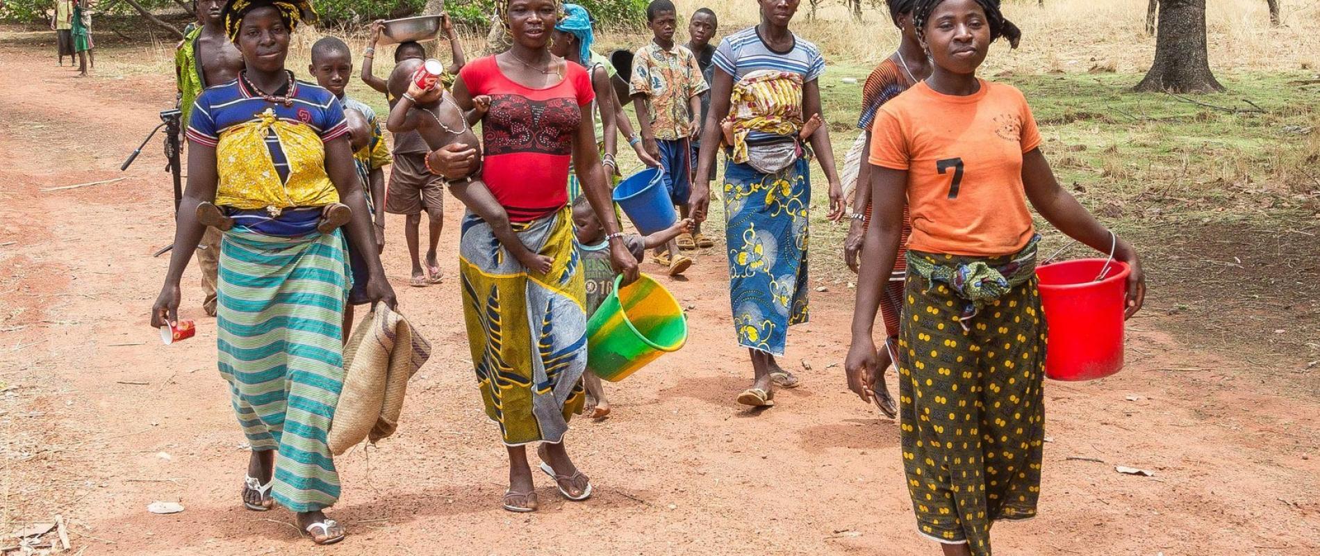 Het begint allemaal op het veld bij de boer, die een cashewboompje plant. Na enkele jaren is het stekje uitgegroeid tot een boom en kan er geoogst worden. Deze vrouwen zijn onderweg naar het veld om te oogsten.