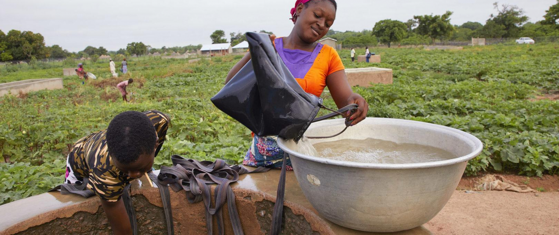 Benin SinendeJacqueline Kora (22) oranje  Tuin van Gnangbannou met waterpomp Dedras 23-6-2018 foto Jaco Klamer