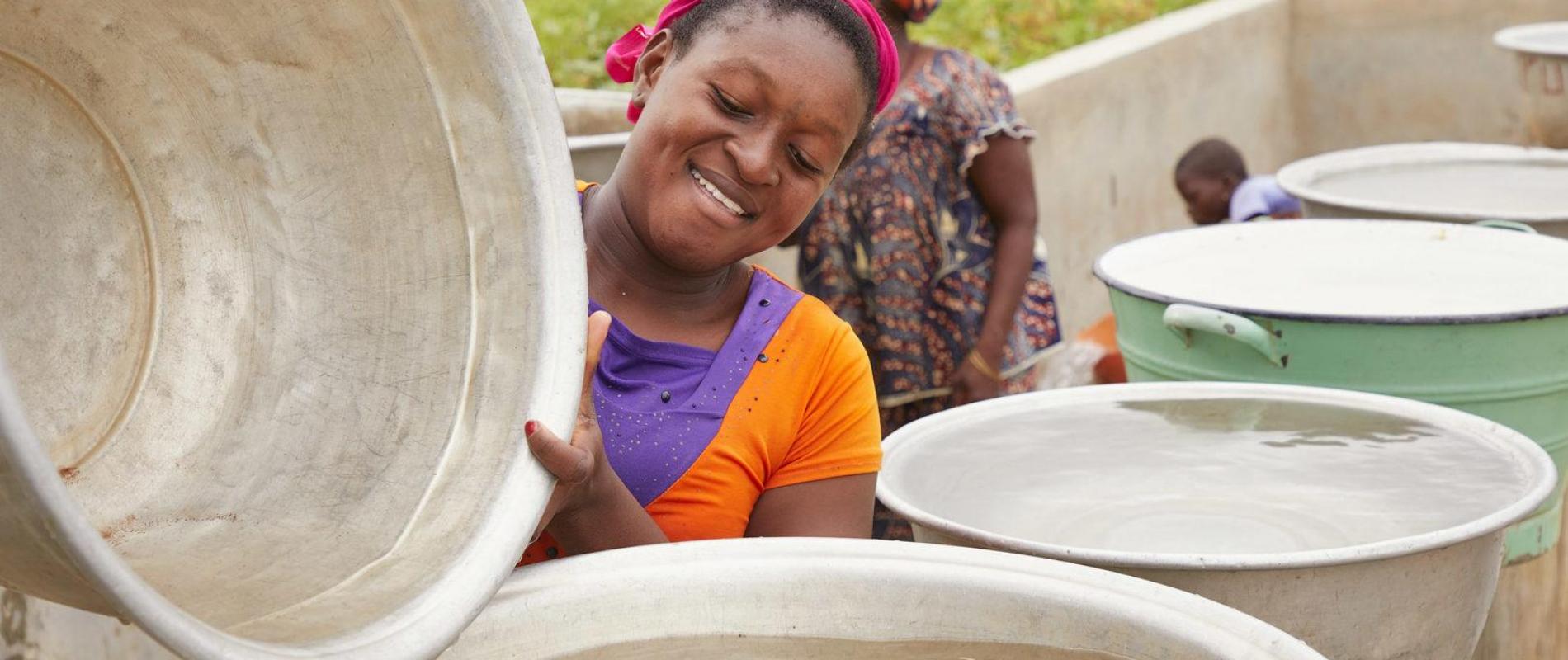 Benin Sinende Jacqueline Kora (22) oranje  Tuin van Gnangbannou met waterpomp Dedras 23-6-2018 foto Jaco Klamer