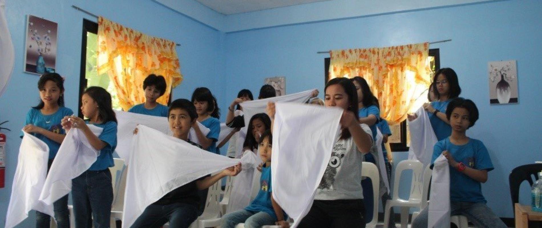 Tijdens de EHBO training leerden de kinderen een mitella omdoen.