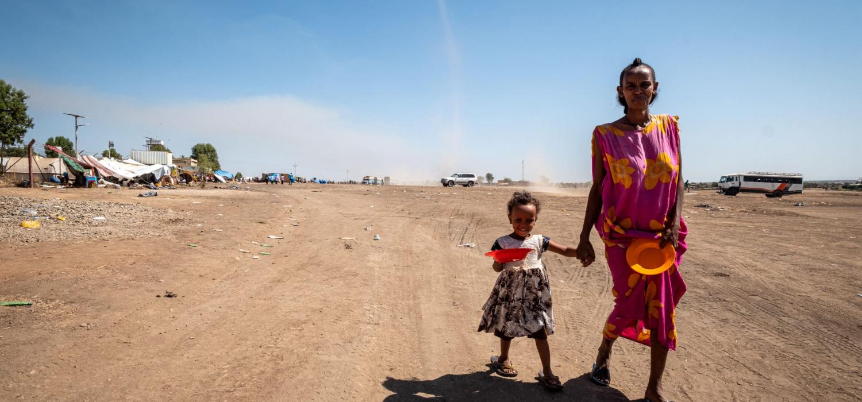 Moeder en dochter, vluchtelingen uit tigray, lopen met lege bordjes naar voedseldistributie in gedaref, sudan
