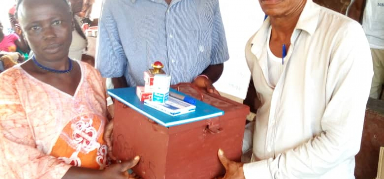 Augustine overhandigt een kist met materiaal aan een boer.